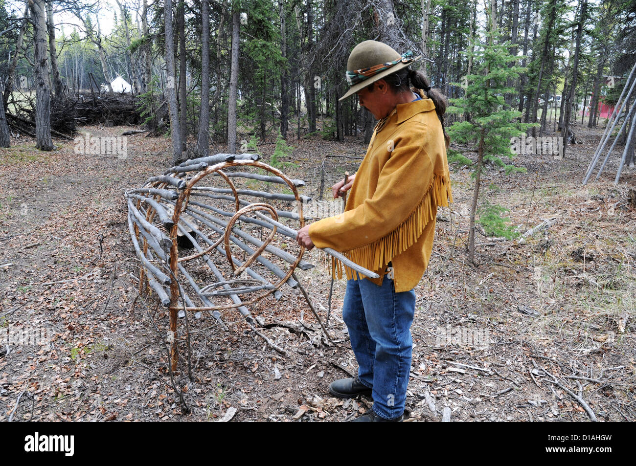 An indigenous elder of Champagne-Aishihik First Nation displays a traditional wooden salmon fish trap in Champagne, Stock Photo