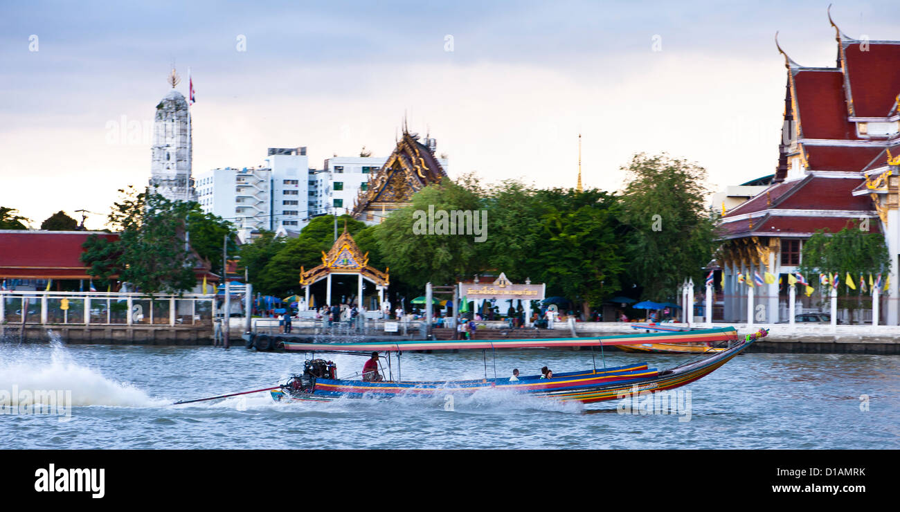 A long tail boat speeds past the  temple of Bells on the Chao Phraya, Bangkok - Stock Image