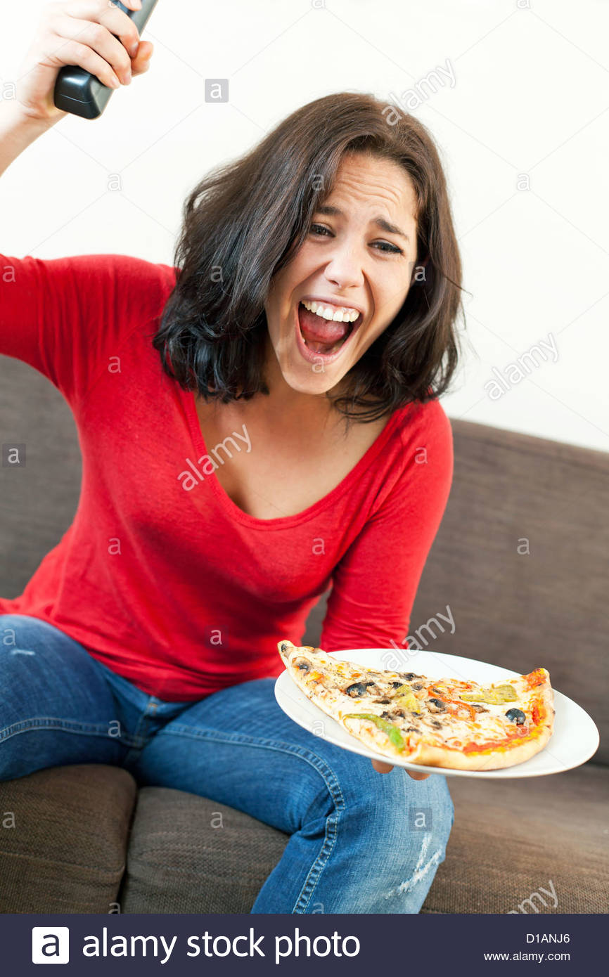 Beautiful young woman exciting in front of television - Stock Image