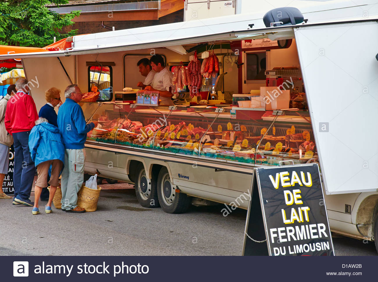 two french butchers selling meat to customers from a mobile butchers van in open air outdoor french market la clusaz Stock Photo