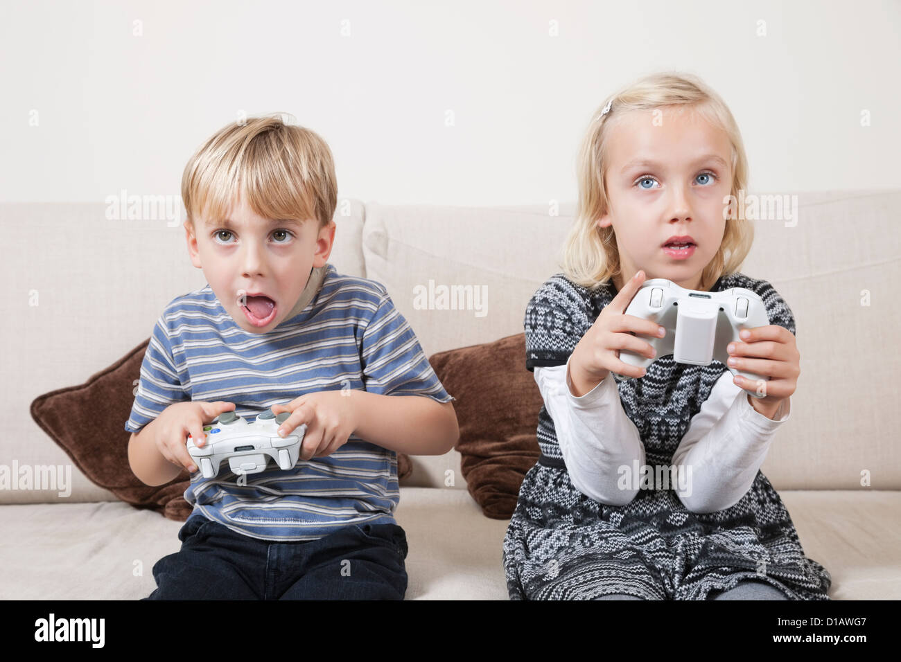 Young brother sister playing video game - Stock Image