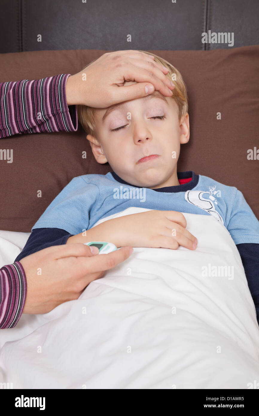 mother rmometer checking little boy's temperature - Stock Image