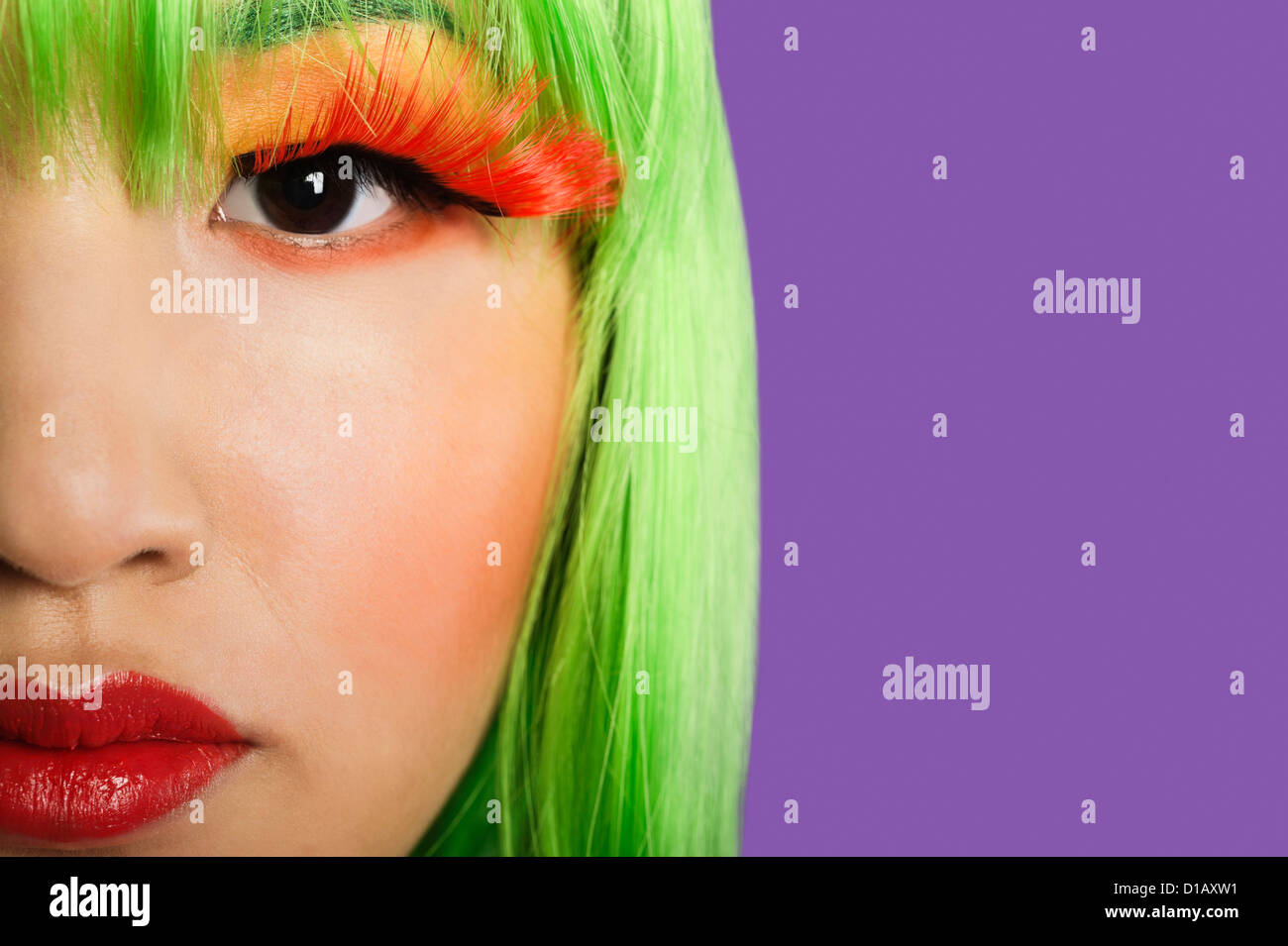 Cropped image young woman wearing false eyelashes  purple background - Stock Image