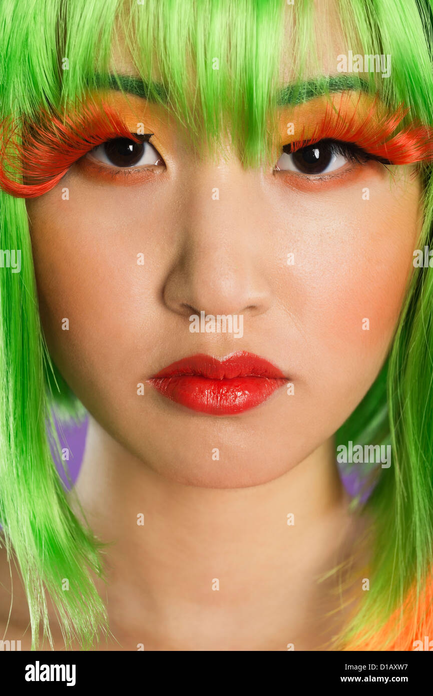 Portrait young woman wearing green wig orange eyelashes over Stock Photo