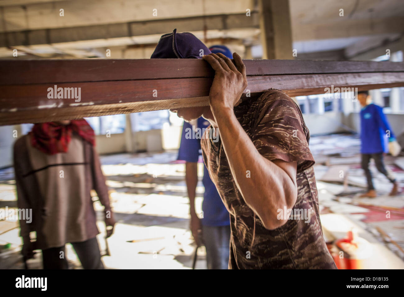 Dec. 13, 2012 - Bangkok, Thailand - A worker carries lumber to be recycled out of an empty building that is being - Stock Image