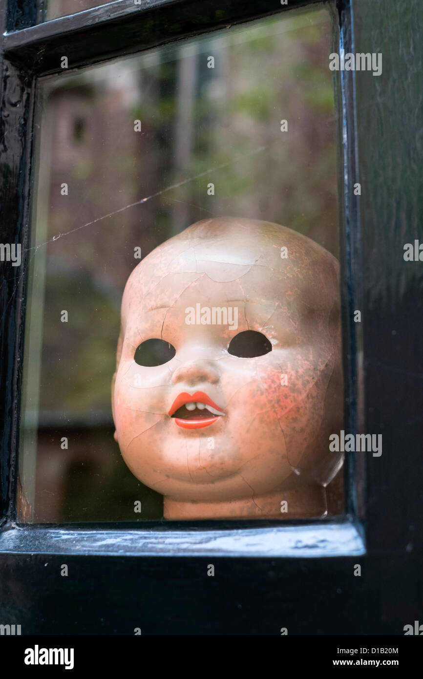 Old doll head on display in antique shop in Nijmegen in The Netherlands - Stock Image