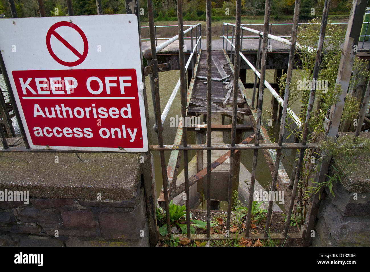A sign saying Keep Off Authorised Access Only prohibits entry to a gangway with a huge hole in it - Stock Image