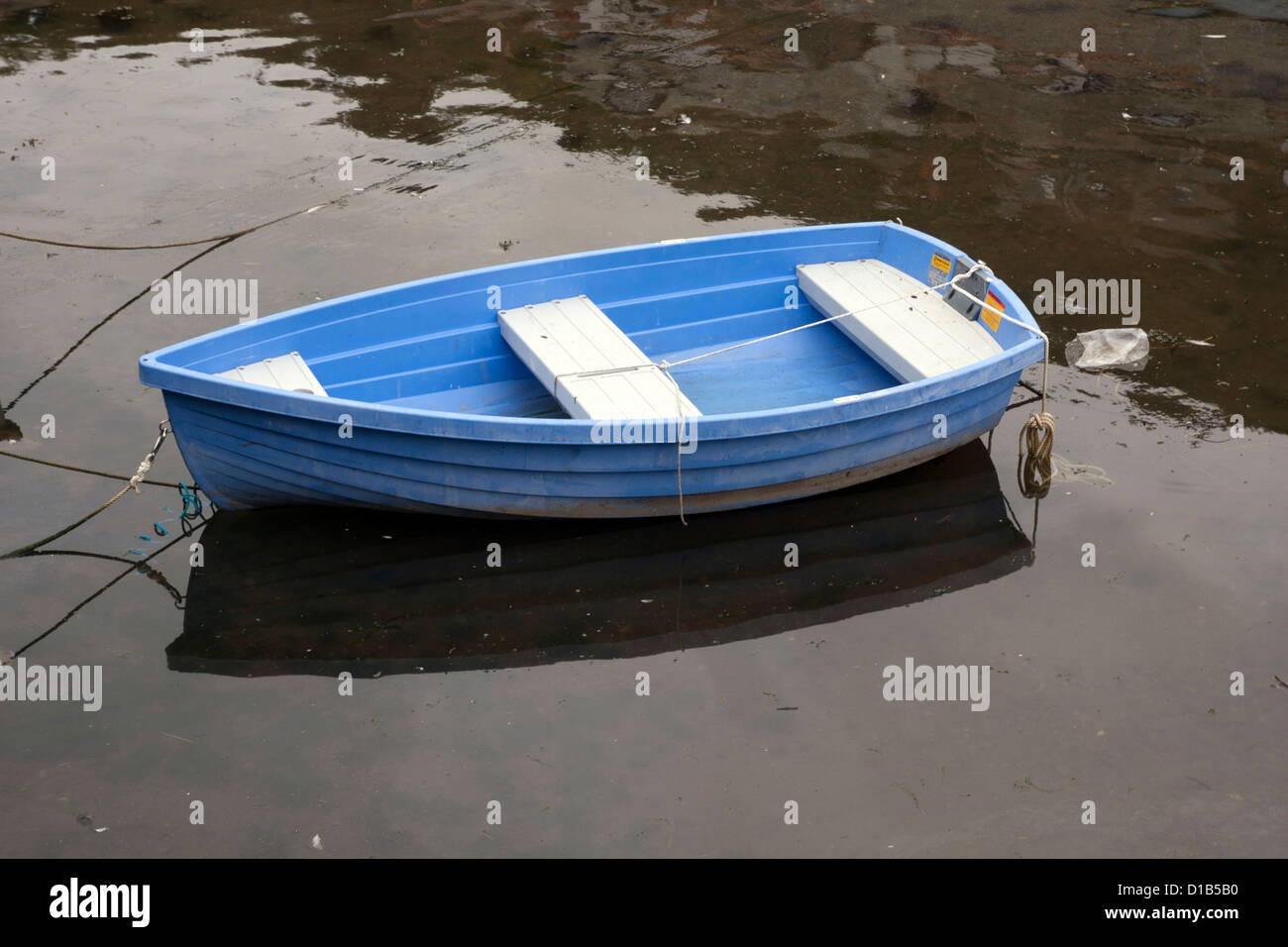 Blue boat floating on stagnant water Stock Photo