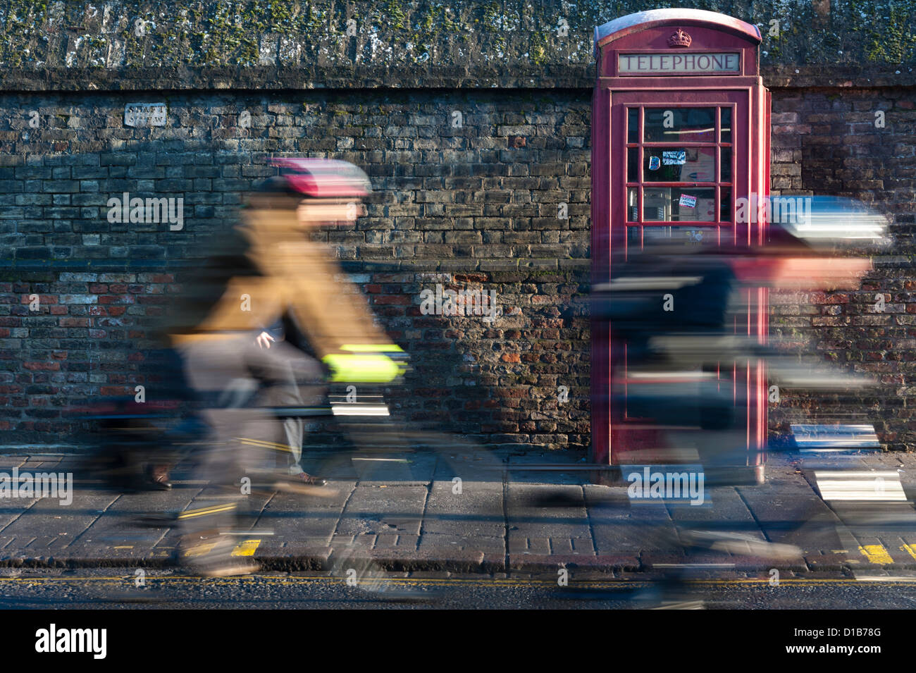 Cyclists with motion blur passing a traditional red telephone box Regent Street Cambridge UK - Stock Image