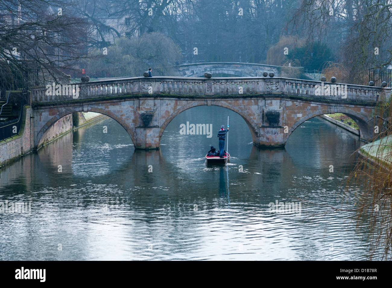 Punting on the River Cam the Backs Cambridge UK on a winter day by Clare College Bridge - Stock Image