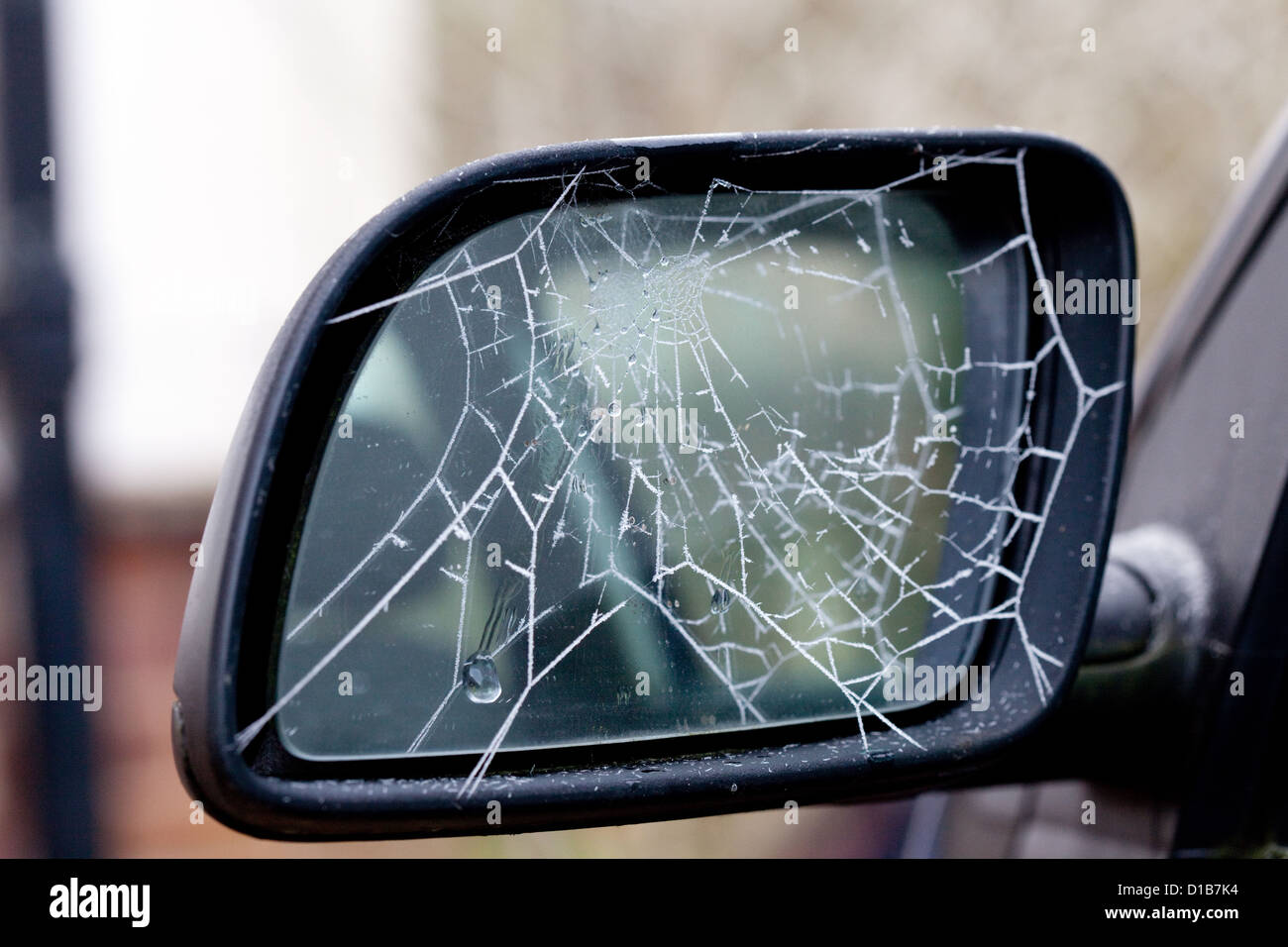 Frost on a cobweb on a car wing mirror symbolising cold weather driving, UK - Stock Image