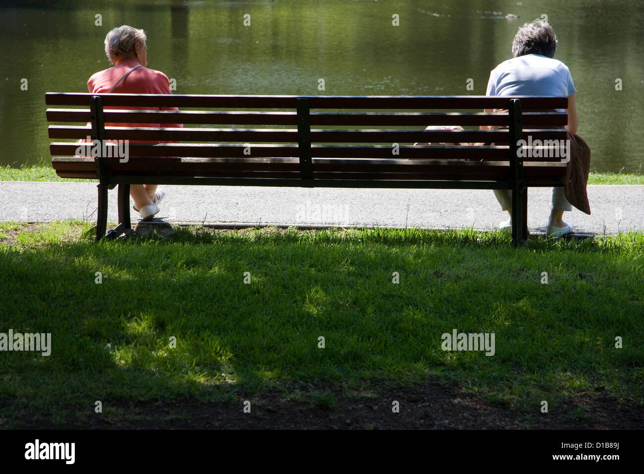 Berlin, Germany, two older women sit separately on a park bench - Stock Image