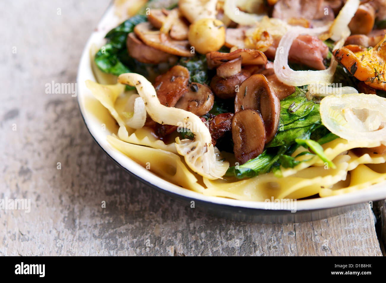 Vegetarian meal with mixed mushrooms, onion and fresh spinach on pasta. Stock Photo