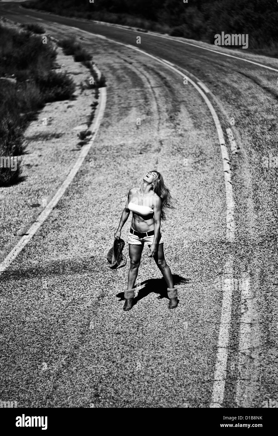 Woman alone on road. - Stock Image