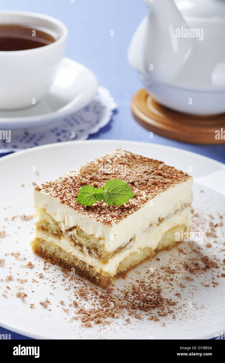 Tiramisu - Classical Dessert with Coffee on white plate. Garnished with Mint. - Stock Image