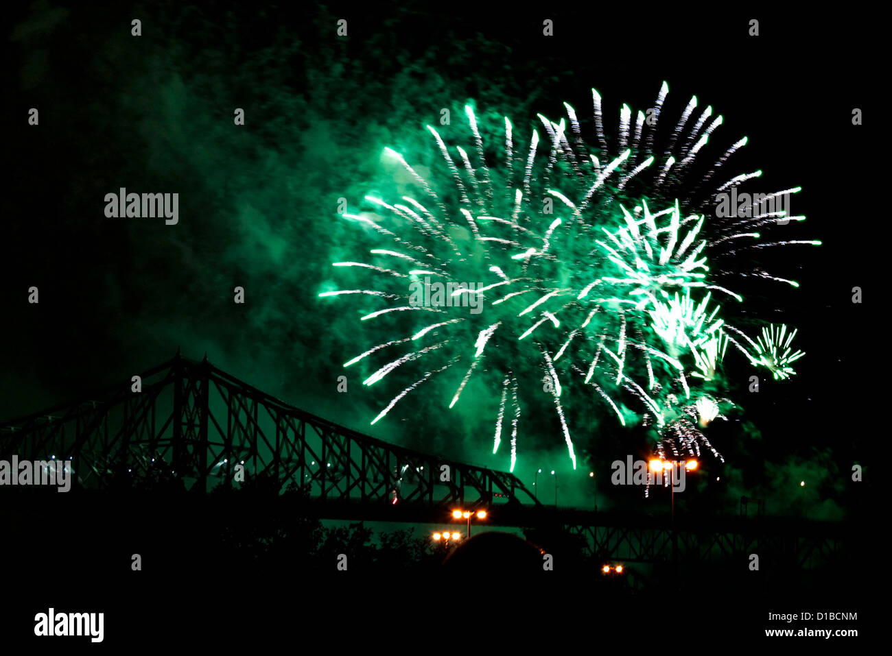 Green fireworks in the night sky near a metal bridge Stock Photo