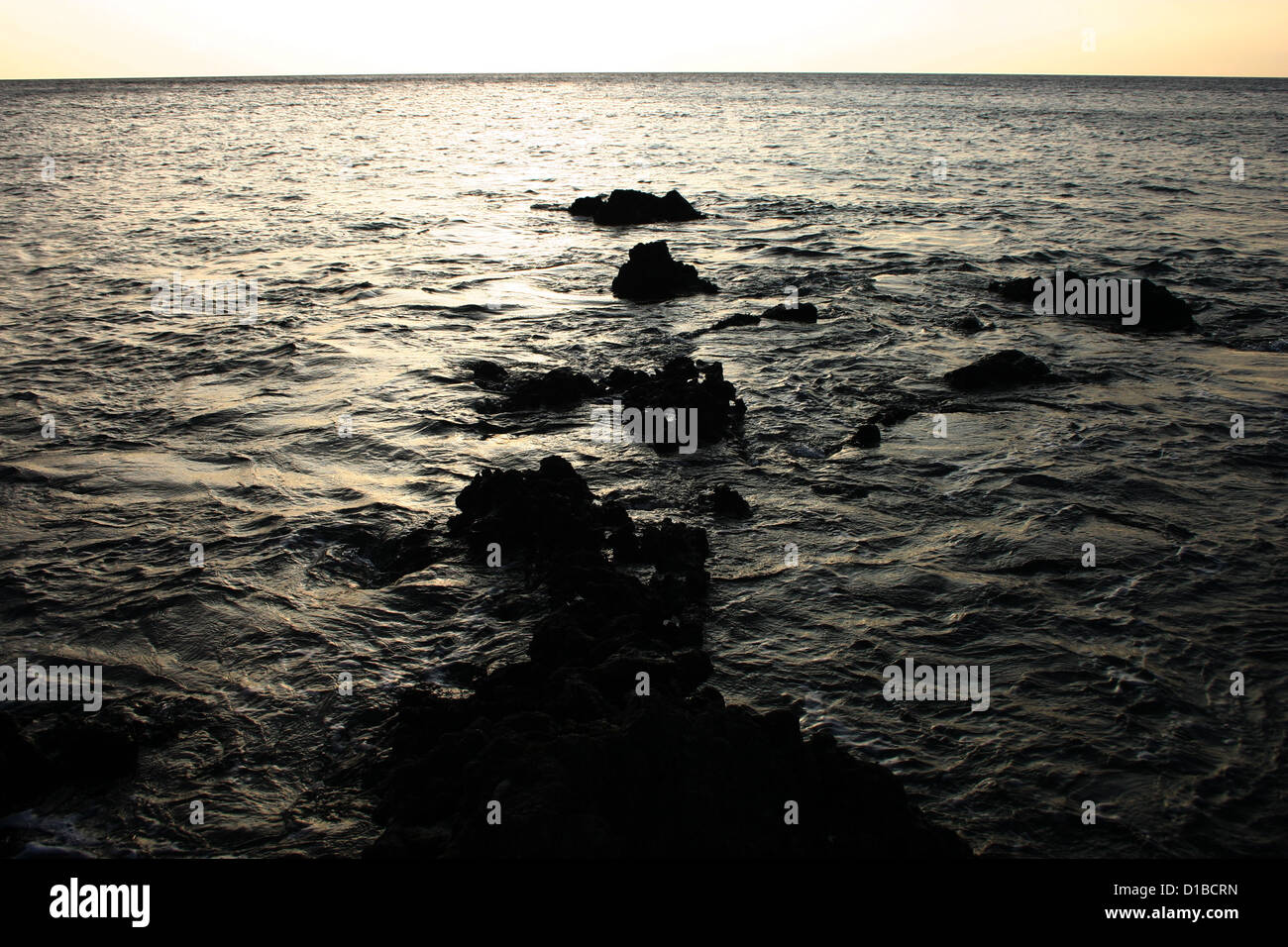 Golden light before sunset over Pacific Ocean from rocky shore, Hawaii, USA Stock Photo