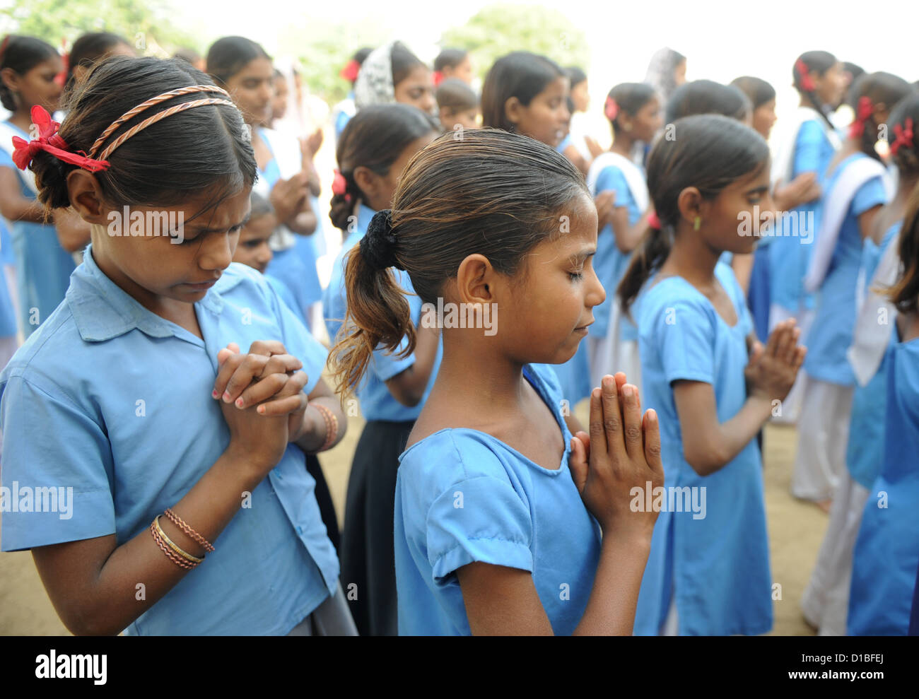 Students pray before the classes start at the girls' school in Mundia near Jaipur, India, 19 November 2012. - Stock Image