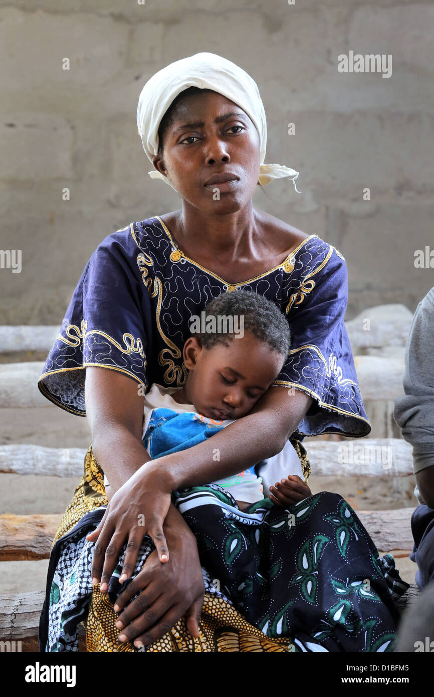 Mother with her sleeping son (fallen ill on Malaria) on a bench in a church in Bagamoyo, Tanzania - Stock Image
