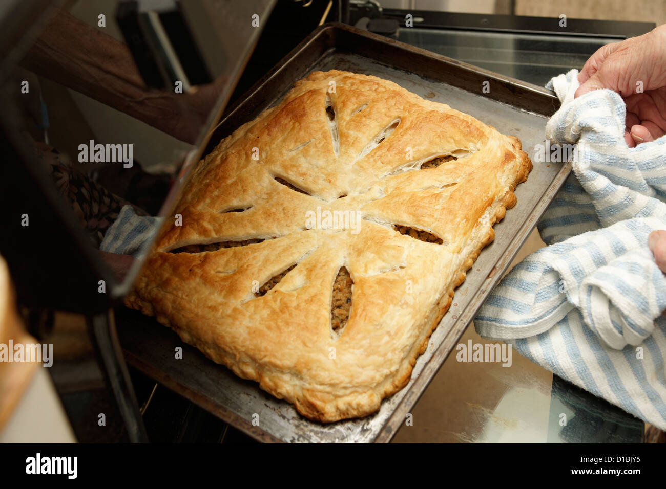 Elderly woman home baking taking a savoury pastry pie out of the oven Stock Photo