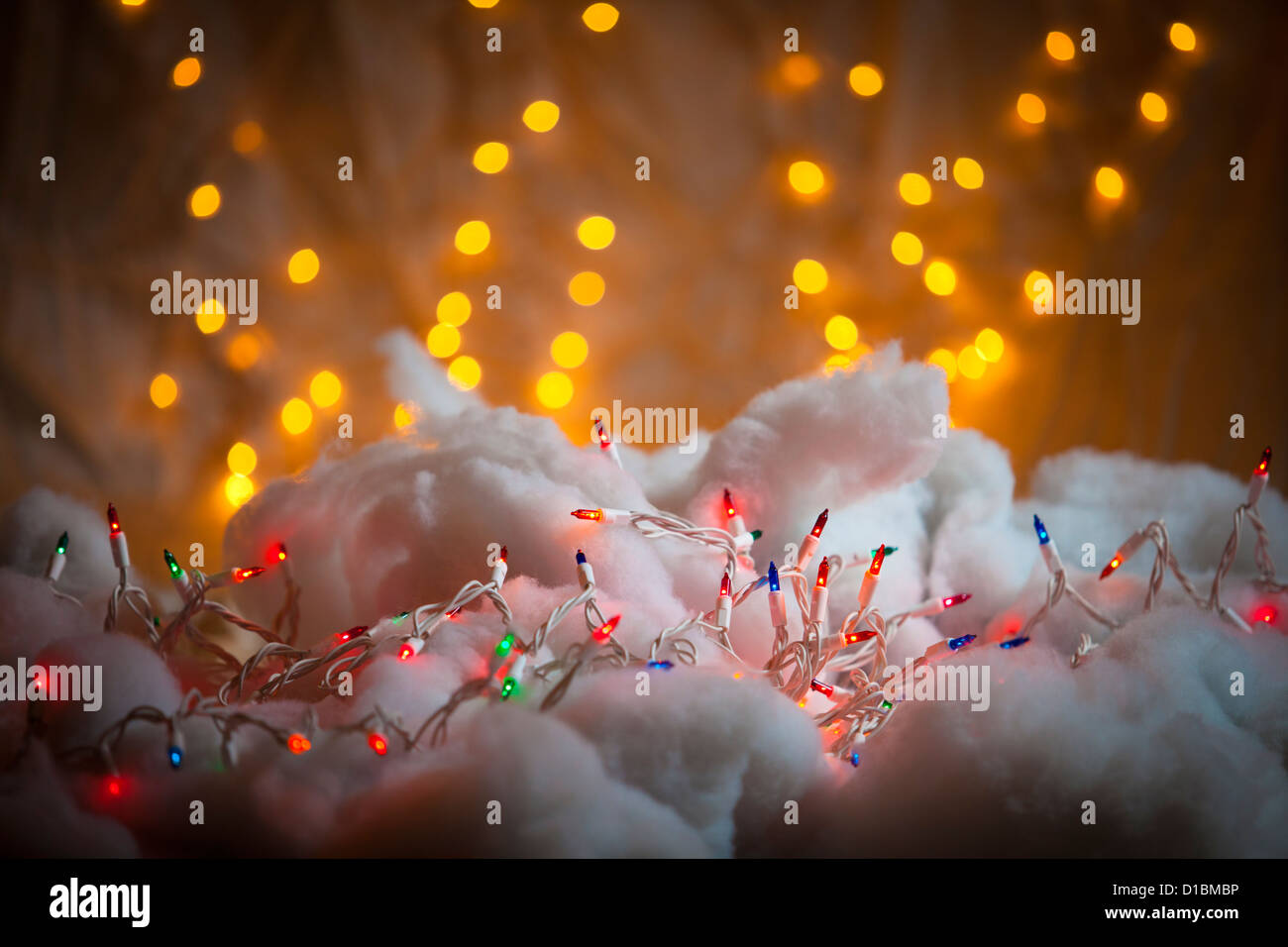 A colorful strand of Christmas lights on snowy fabric - Stock Image