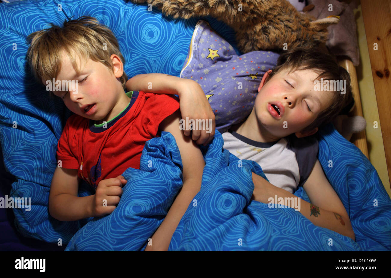 Berlin, Germany, children sleep together in one bed - Stock Image