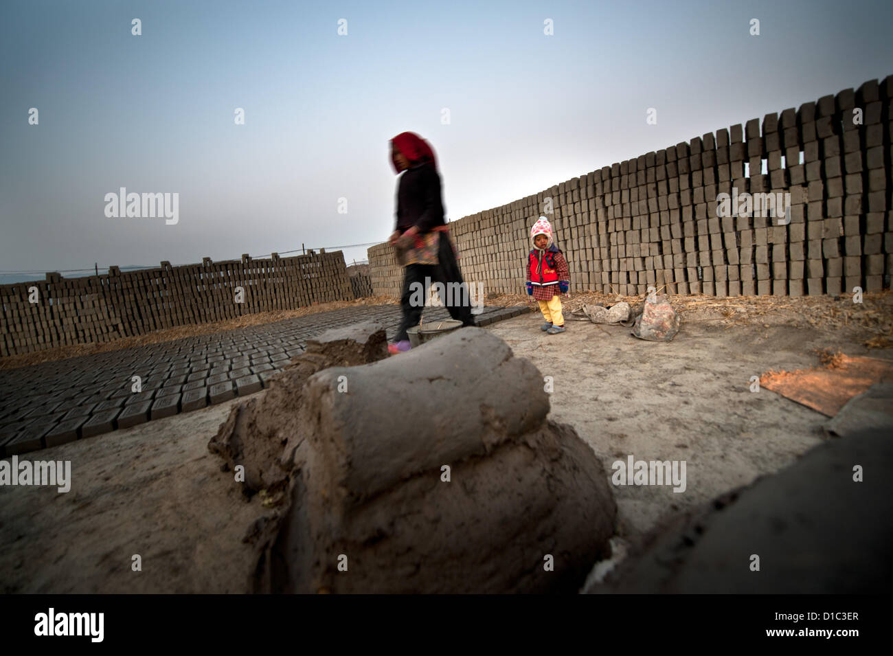 Dec. 14, 2012 - Bakthapur, bakthapur, Nepal - A child stands by the pilled bricks while his parents make bricks..In - Stock Image