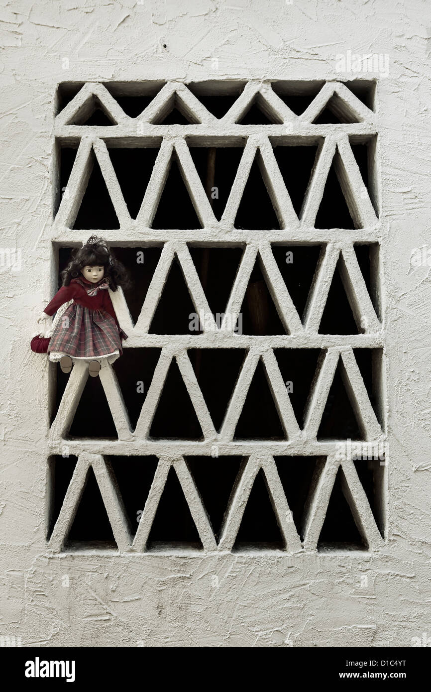 an old doll hanging on a window with a grate - Stock Image