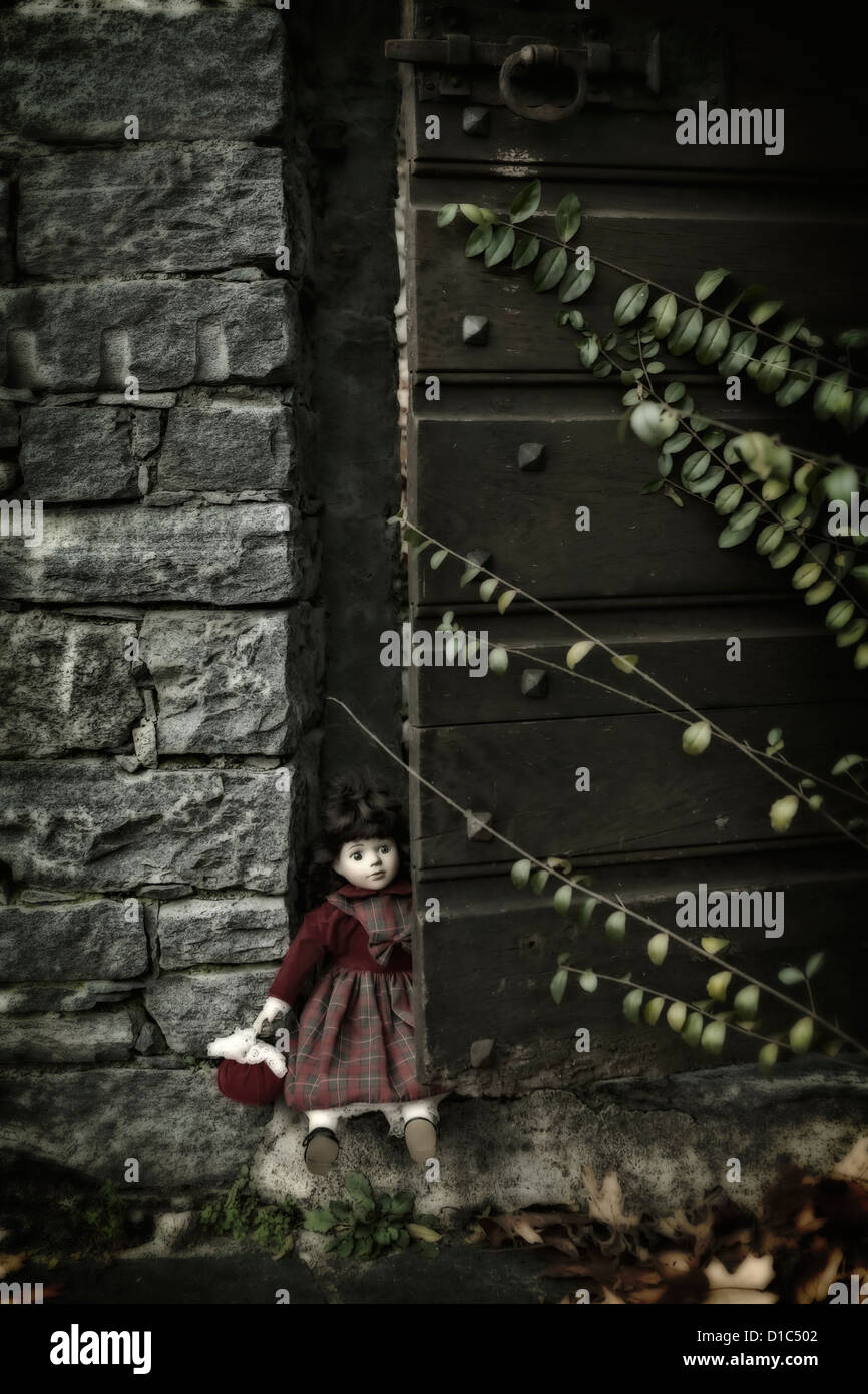 an old doll, sitting in an old wooden door - Stock Image