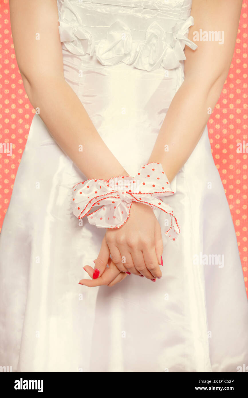 bonded hands of a girl with a polka dotted ribbon - Stock Image