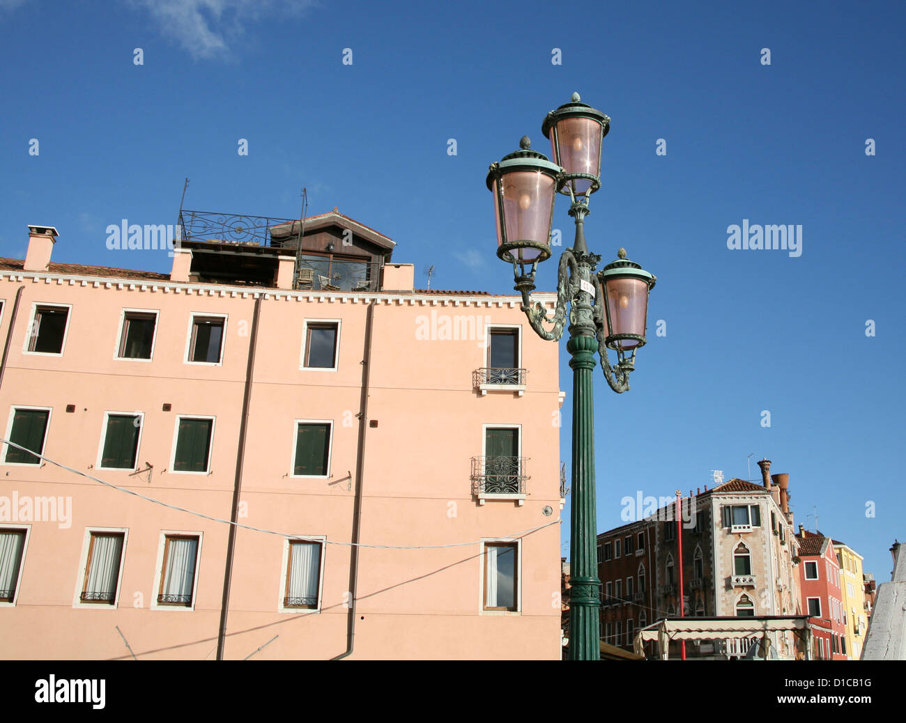 Streetlamp and building under sunny blue sky, Venice, Italy, low angle view - Stock Image