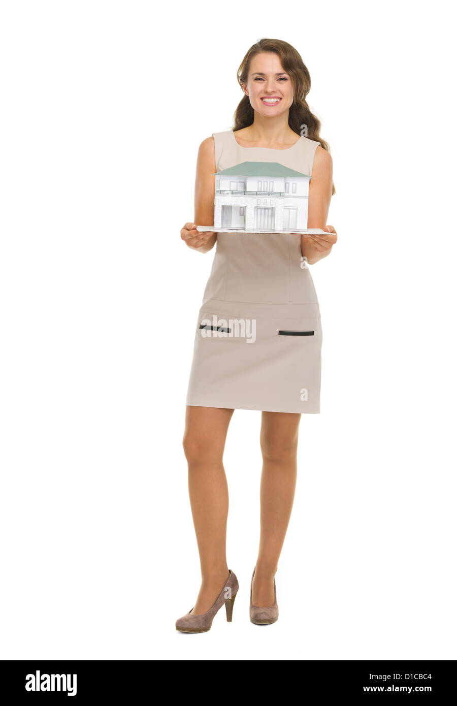 Happy woman homeowner showing scale model of house - Stock Image