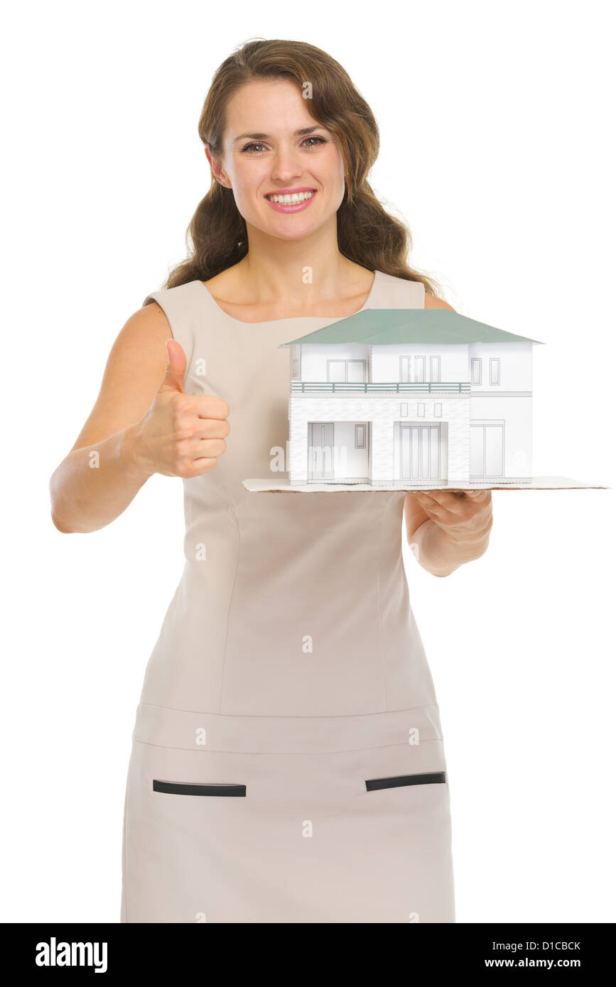 Happy woman landlord with scale model of house showing thumbs up - Stock Image