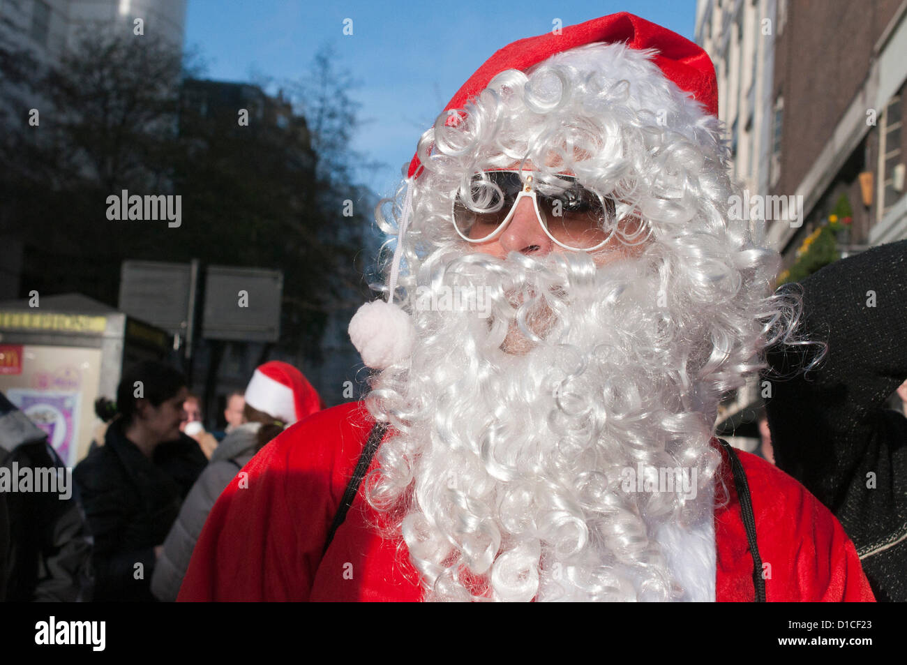 15 December 2012 London UK. Santa looks cool in shades as fancy dressed revellers roam central London during Santacon - Stock Image