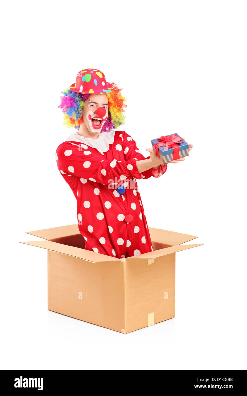 Smiling clown in a cardboard box holding a gift isolated on white background - Stock Image