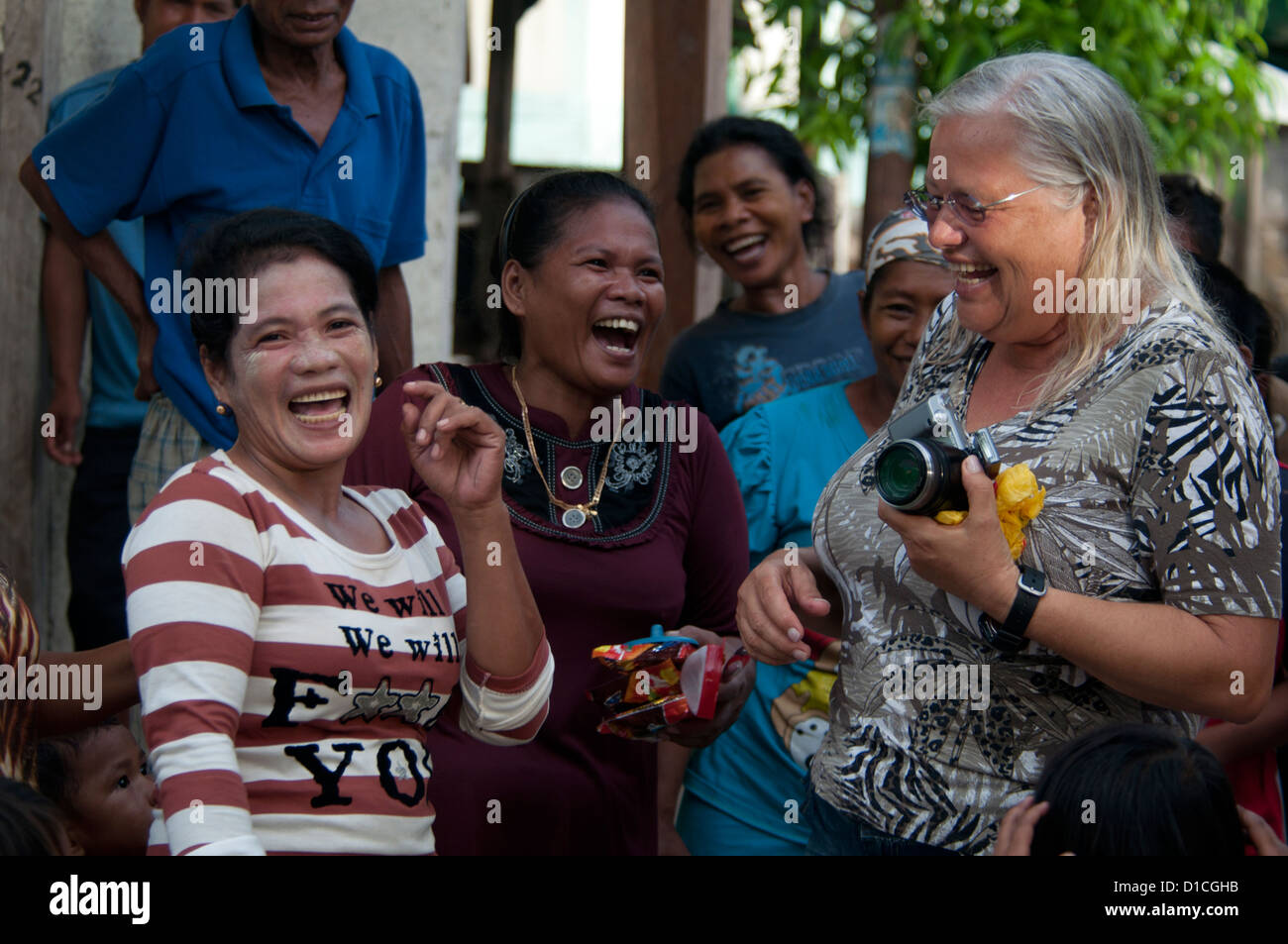 A tourist takes photos of and interacts with the local women of Pau Island village, Ceram, Maluku region, Indonesia, Stock Photo