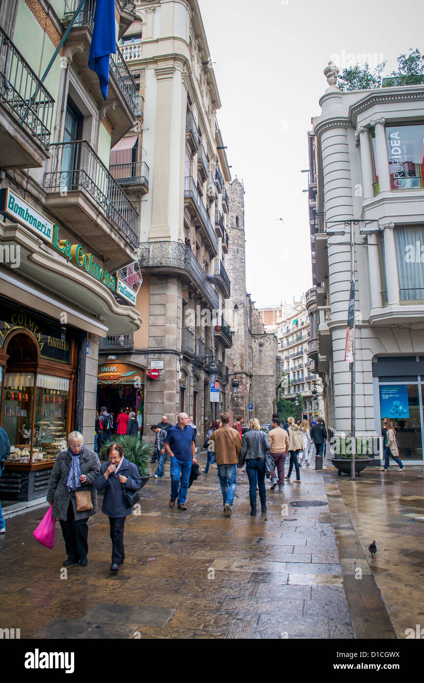 Shoppers and tourists on the streets of Barcelona, Spain on a rainy Sunday afternoon. - Stock Image