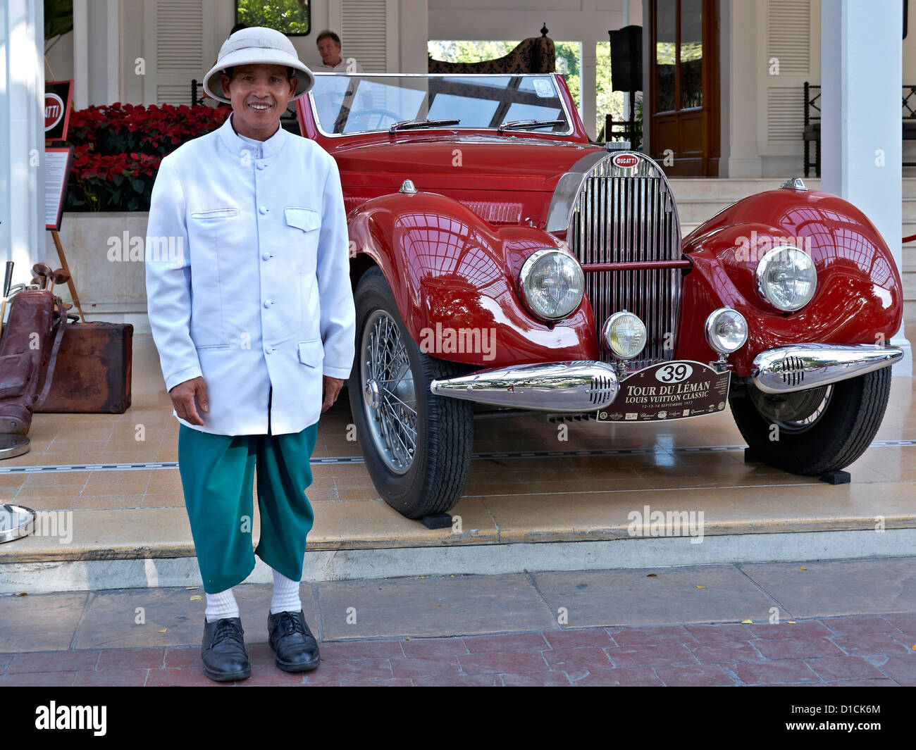 Bellboy at a Thailand hotel and a red Bugatti 1938 model type 57 veteran motor car. Thailand S. E. Asia - Stock Image