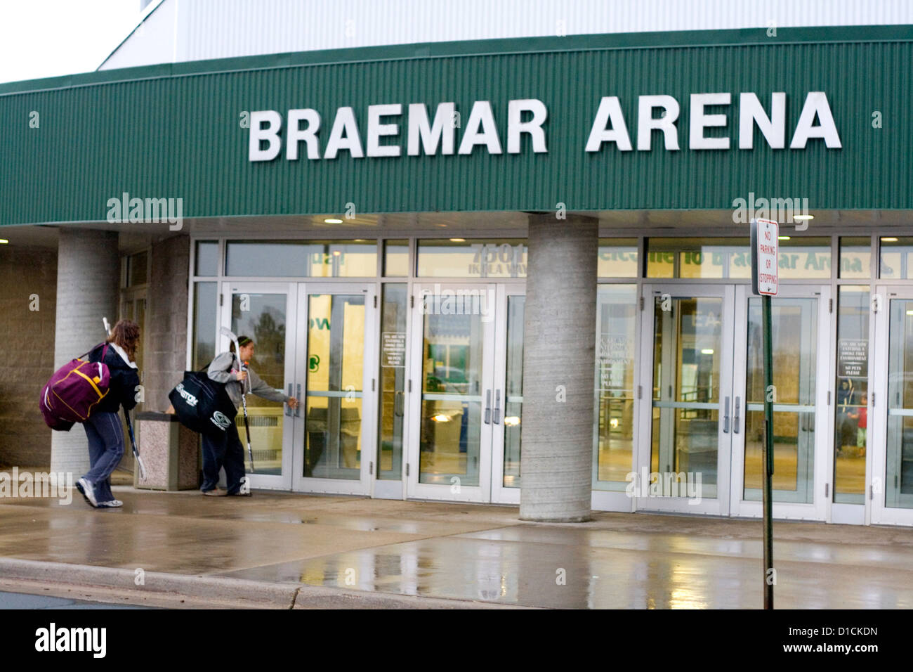 Teen women hockey players entering Braemar Arena for a game. Edina Minnesota MN USA - Stock Image