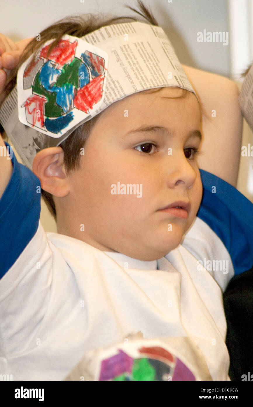 Male first grade student wearing hat with recycle logo during a recycling program. Horace Mann School St Paul Minnesota - Stock Image