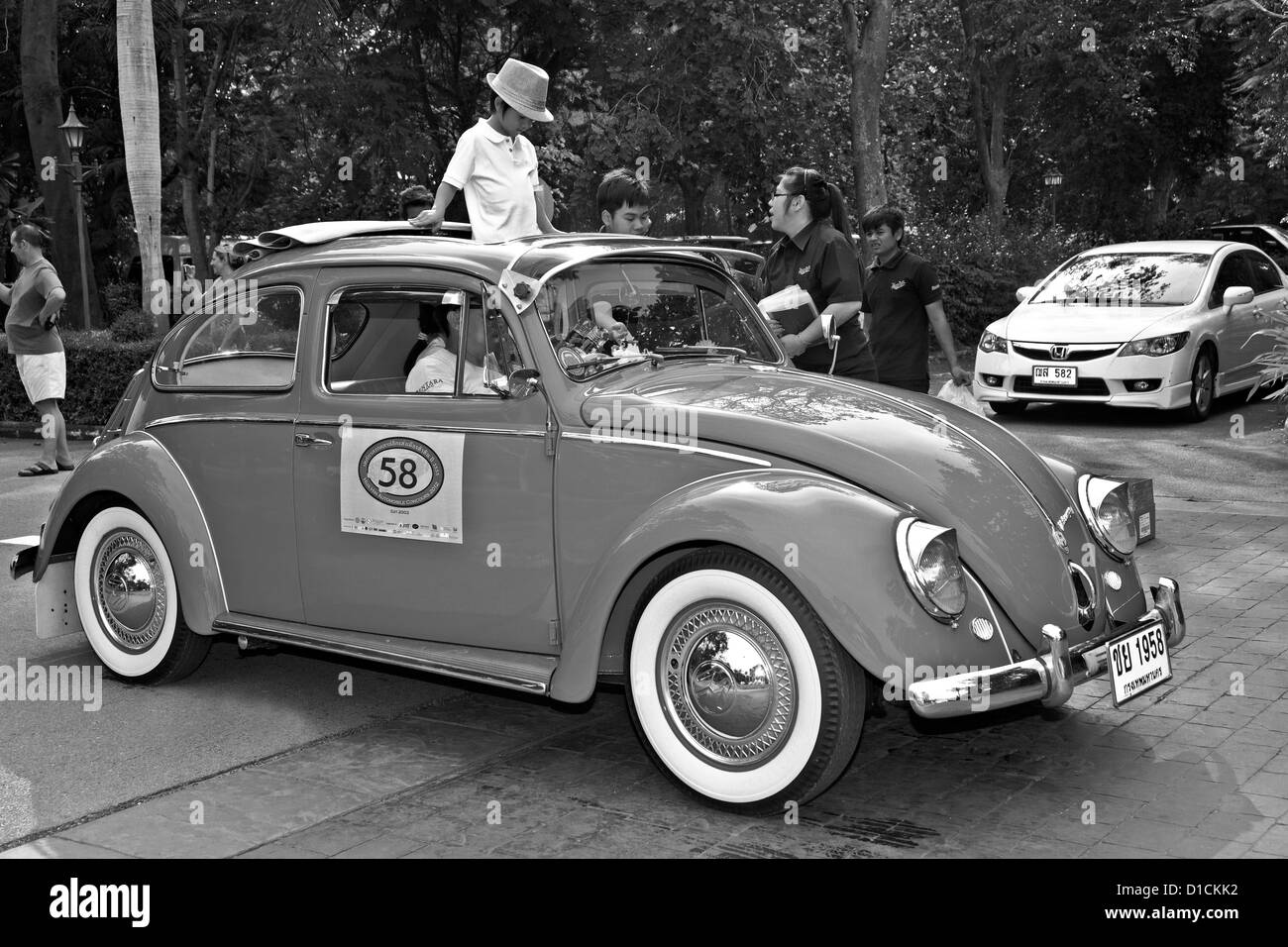 50's Volkswagen Beetle and passengers at a vintage car rally. Thailand S. E. Asia Black and white photography - Stock Image