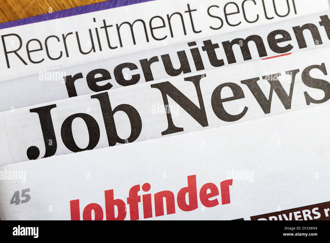 Newspapers stacked up with world news about recruitment issues. - Stock Image