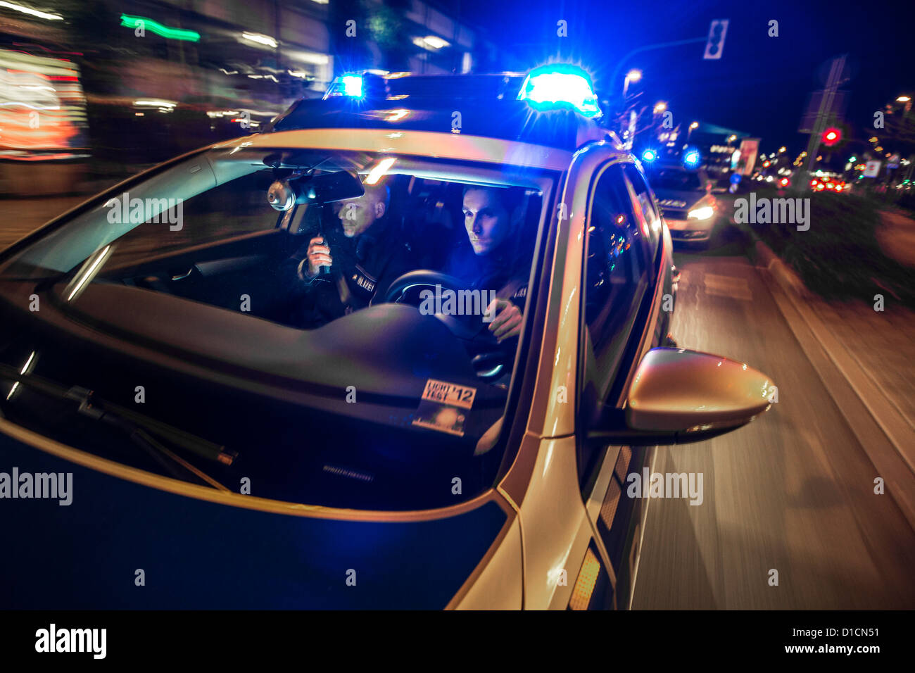 Police patrol car with blue flashing lights, signal horn, driving fast during an emergency mission. - Stock Image