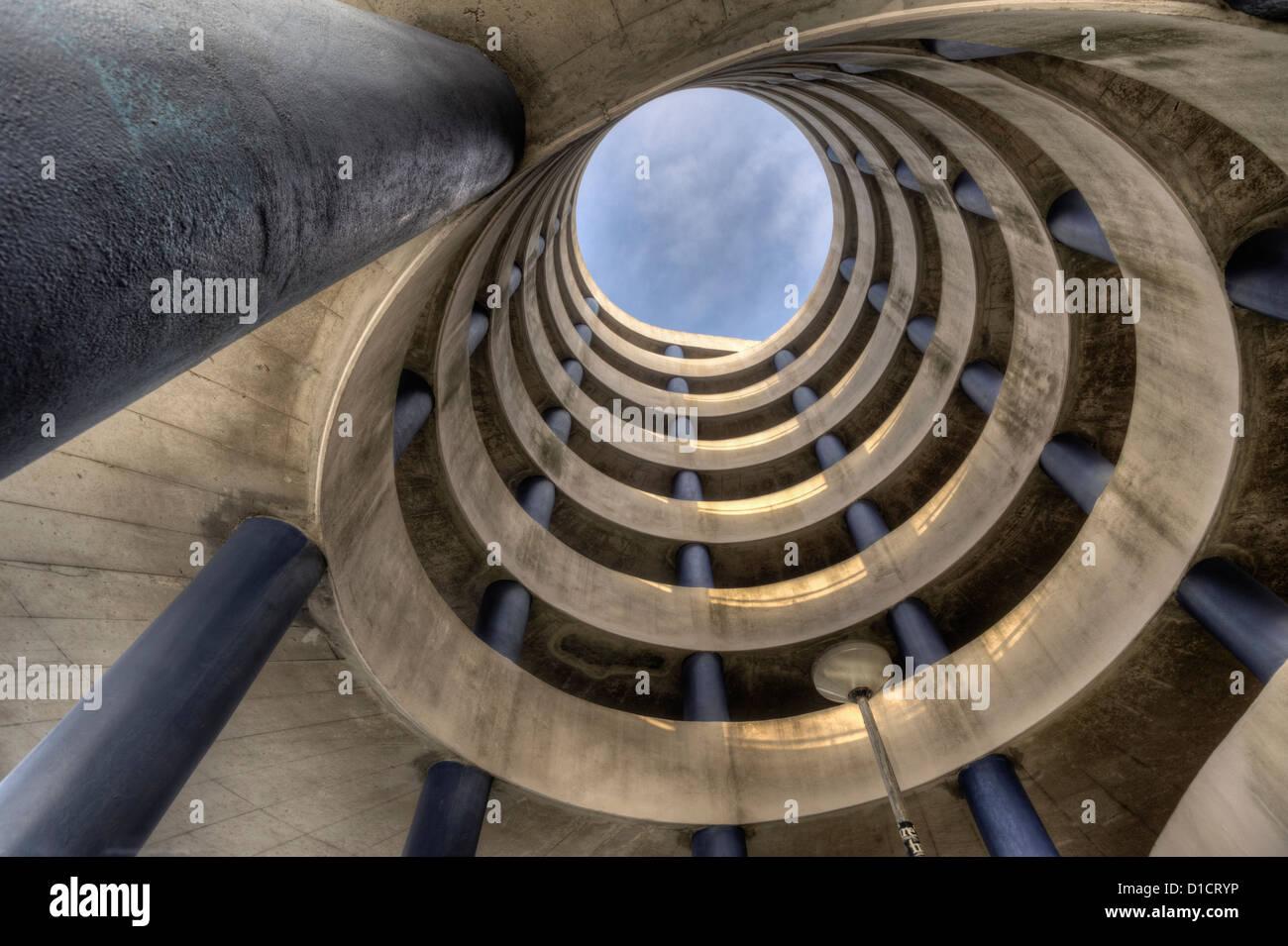 Spiraling concrete ramps of a large parking garage - Stock Image