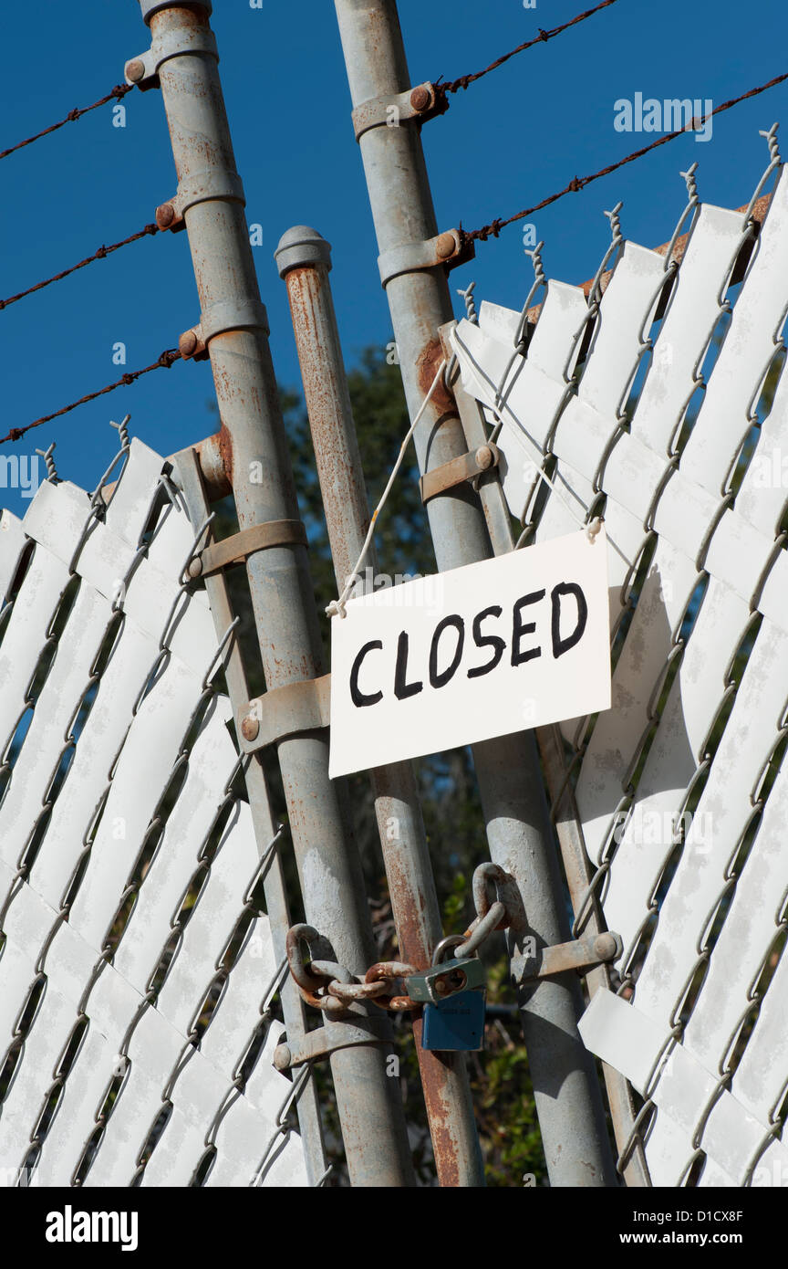 closed sign on padlock chain link fence factory gate - Stock Image