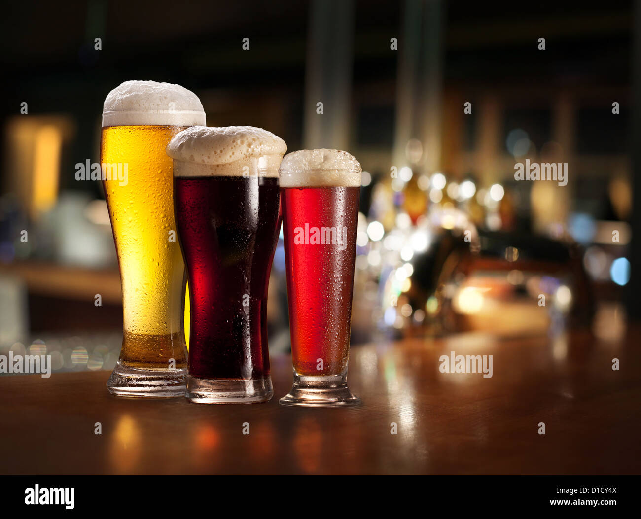 Glasses of light and dark beer on a pub background. - Stock Image