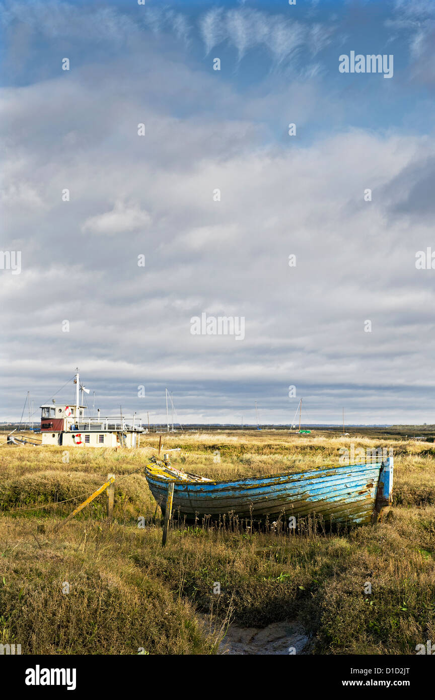 An old wooden dinghy abandoned in the Tollesbury Saltings in Essex. - Stock Image