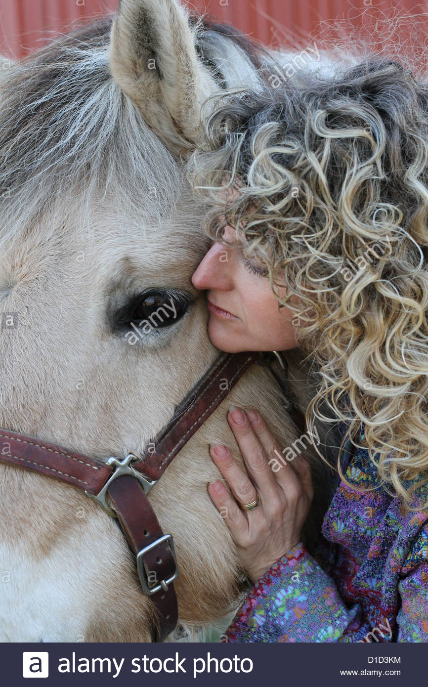 A woman next to a draft horse. - Stock Image