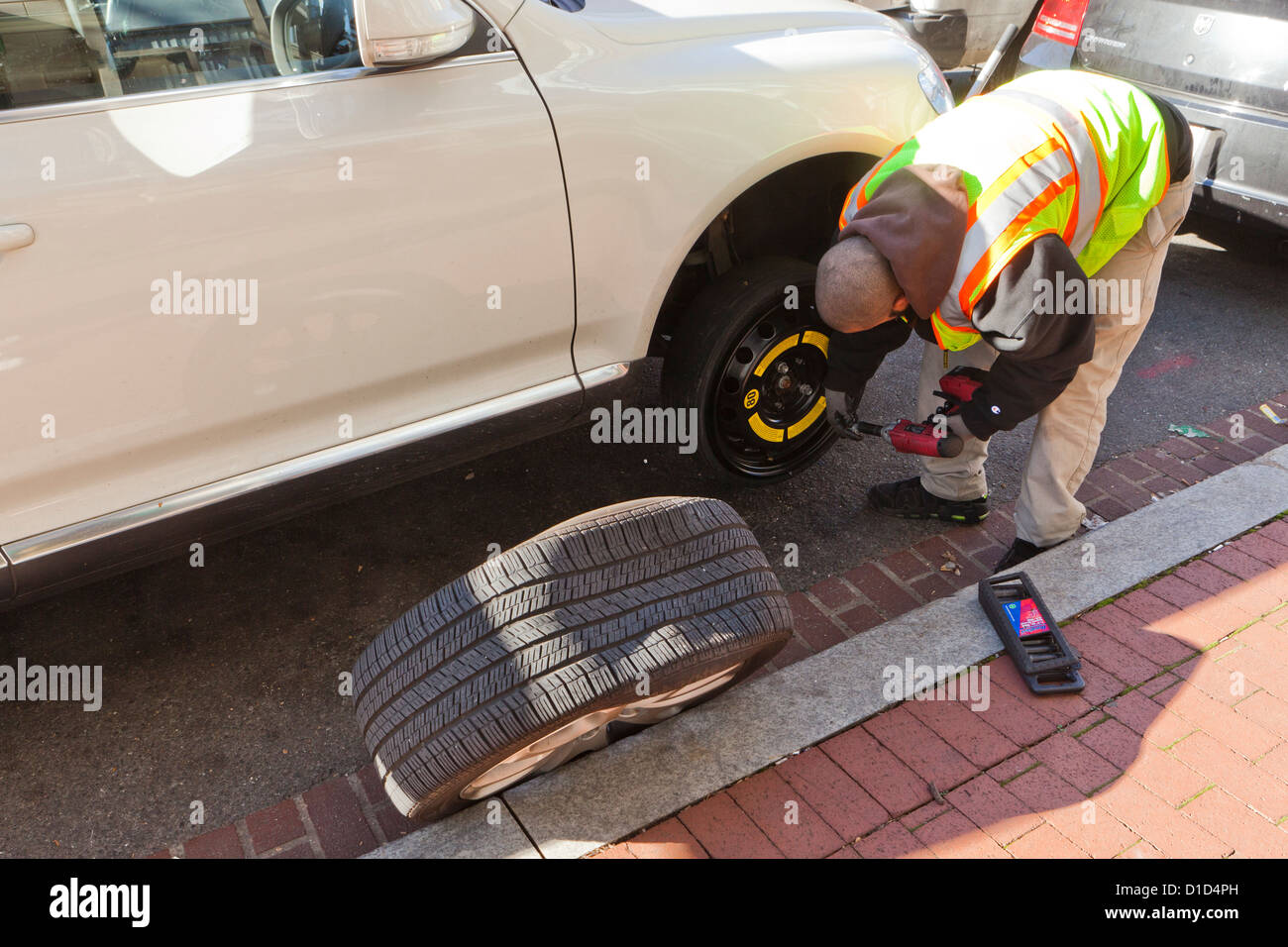 Man changing a flat tire - Stock Image