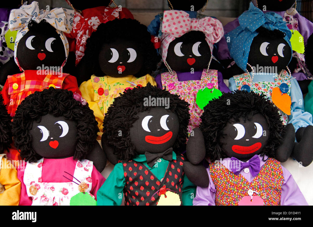 Group of smiling golliwogs with bright and colourful clothing - hand-made toys Stock Photo